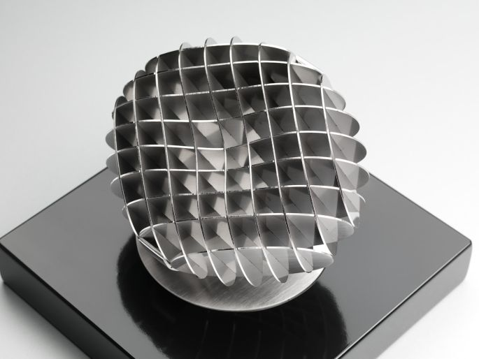 Slot construction form, stainless steel, catches and reflects light, creates patterns of light and shadow.